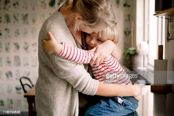 loving daughter embracing mother while sitting on kitchen counter at home - love emotion stockfoto's en -beelden
