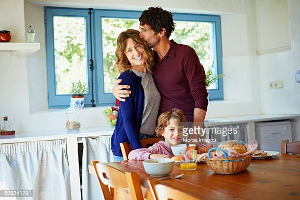 Loving family at breakfast table in kitchen