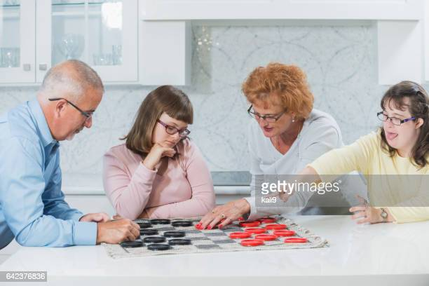 Loving family, daughters with down syndrome playing game