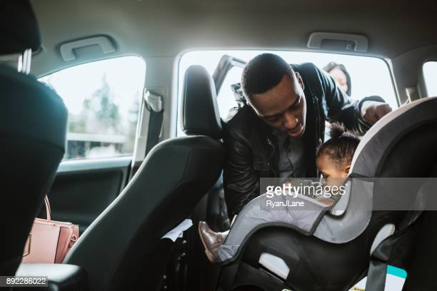 Loving Father Buckles Daughter in Car Seat