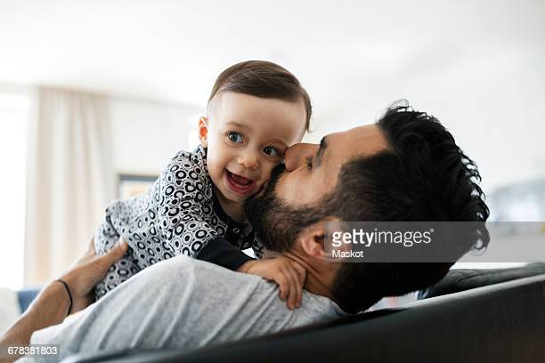 loving father kissing baby girl while sitting on sofa at home - leanincollection stock pictures, royalty-free photos & images