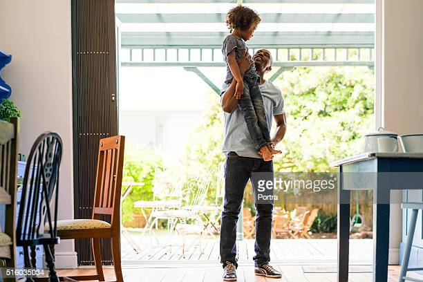 Loving father lifting girl at home