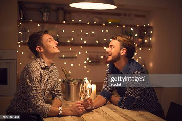 Loving gay couple drinking champagne.