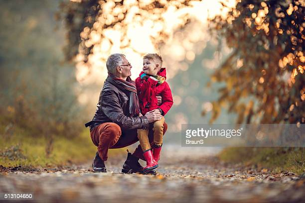 Loving grandfather and grandson talking to each other in autumn.