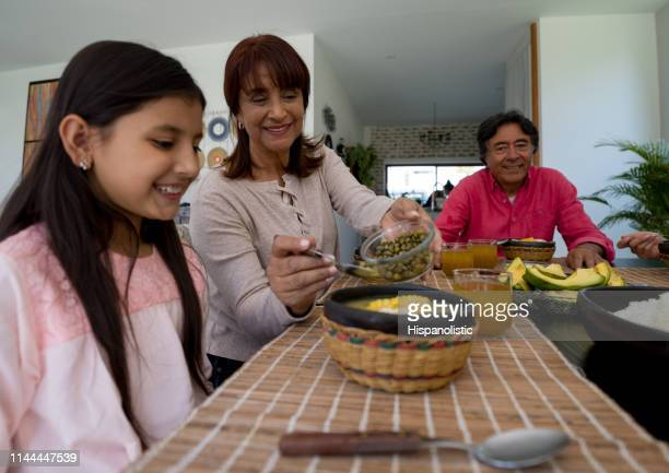 loving grandmother adding capers to her granddaughter's ajiaco all enjoying a family lunch - rice food staple stock pictures, royalty-free photos & images