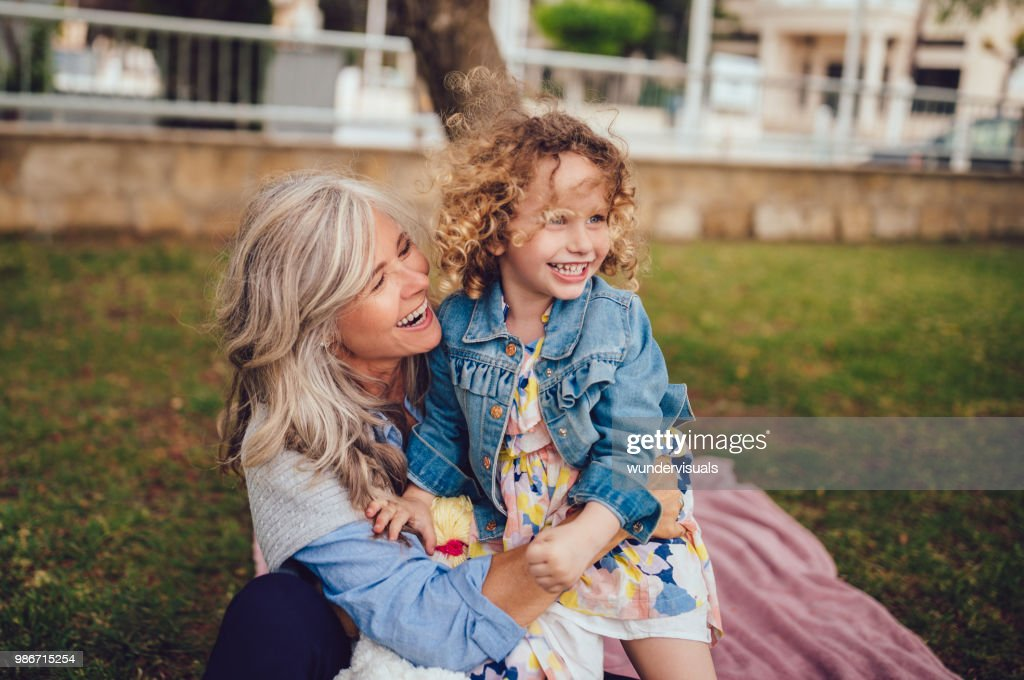 Loving grandmother and granddaughter playing and laughing together in garden : Stock Photo
