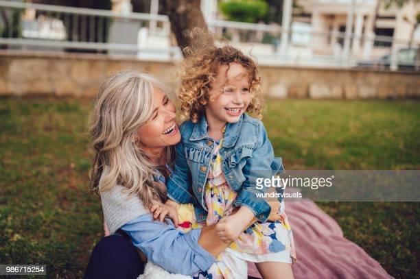 loving grandmother and granddaughter playing and laughing together in garden - grandmother stock pictures, royalty-free photos & images