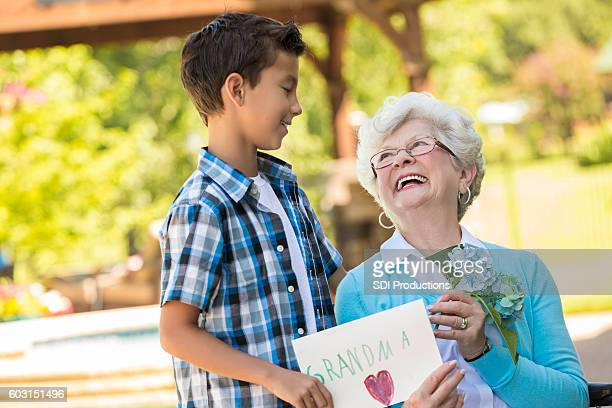 Loving grandmother looks up at her grandson