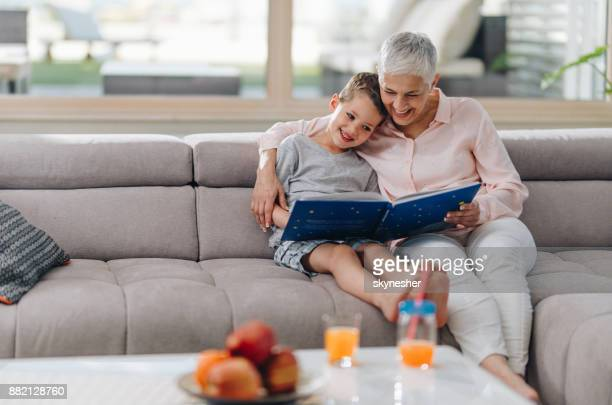 Loving grandmother reading a book to her grandson at home.