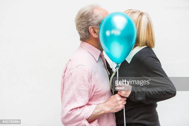 Loving Happy Active Senior Couple Playing With Balloons