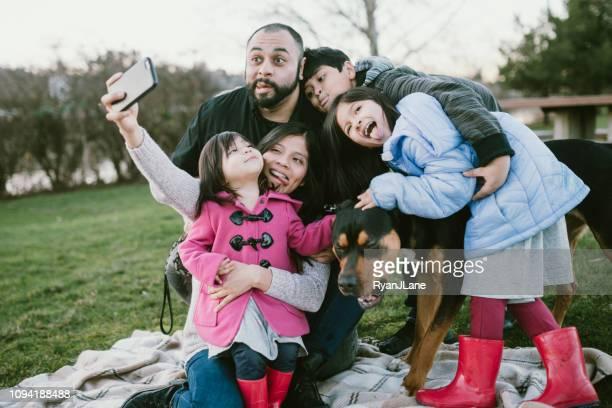 liefdevolle spaanse familie die selfie met huisdier hond - nosotroscollection stockfoto's en -beelden