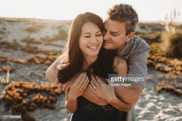 loving husband with closed eyes embraces beautiful smiling wife - wife stock pictures, royalty-free photos & images
