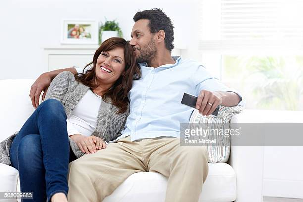 Loving interracial couple sitting on sofa watching TV
