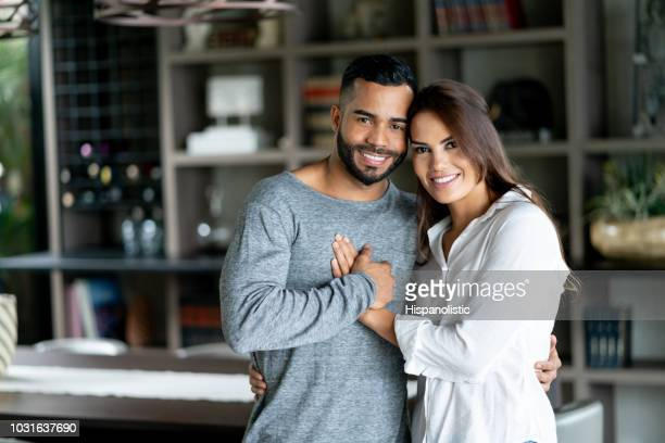 Loving latin american couple at home embracing each other while looking at camera very happy