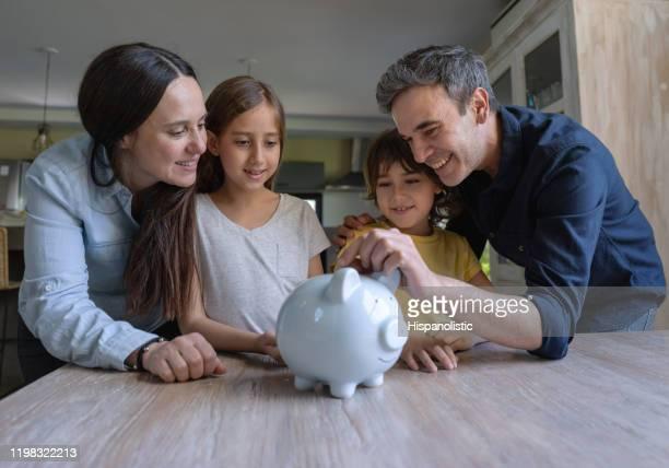 liebende lateinamerikanische eltern lehren ihre kinder, geld in einem sparschwein zu sparen - ersparnisse stock-fotos und bilder