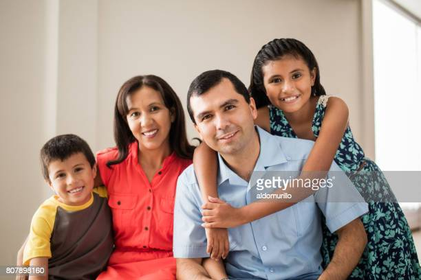 Loving latin family with two children smiling at camera