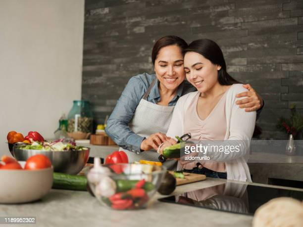 loving latin mother teaching daughter to cook at home - mexican culture stock pictures, royalty-free photos & images