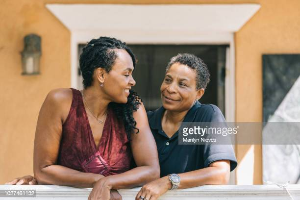 loving lesbian couple posing on the porch - lgbtq  and female domestic life stock pictures, royalty-free photos & images