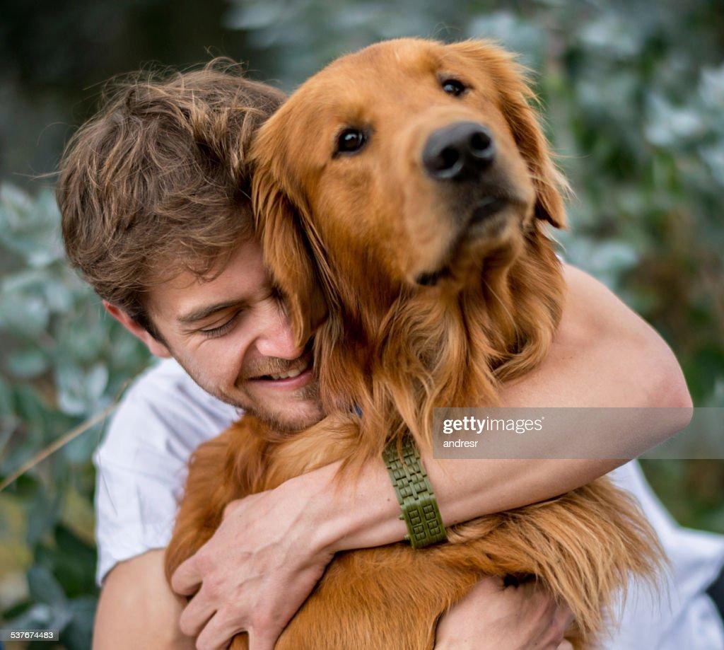 Loving man hugging his dog : Stock Photo