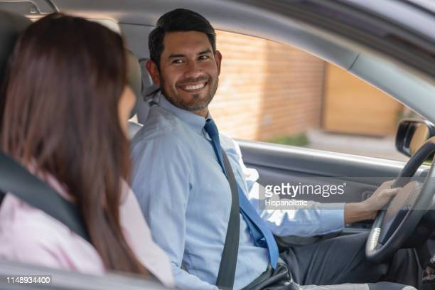 Loving man looking at his spouse while both sitting on car smiling