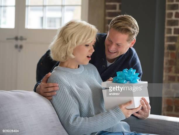 Aimer l'homme surprenant sa compagne en lui donnant un cadeau alors qu'elle a l'air étonné et excité