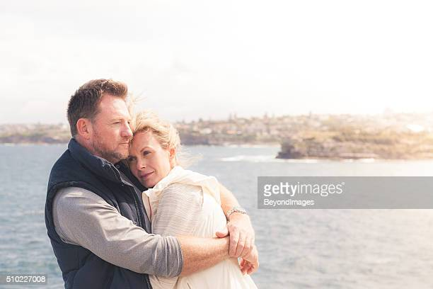 Loving mature adult couple embracing in warm coastal sun