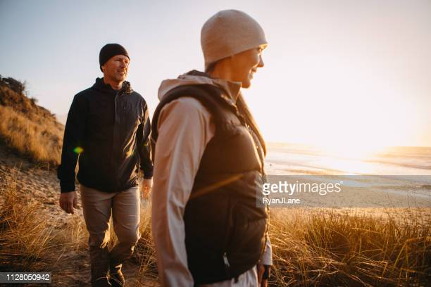 loving mature couple hiking at oregon coast - winter coat stock pictures, royalty-free photos & images