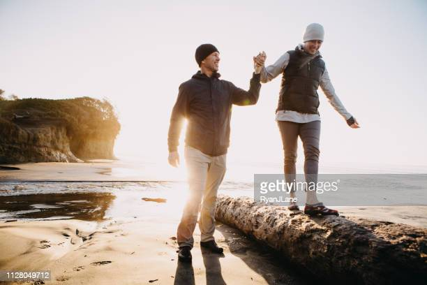 loving mature couple playing at oregon coast - balance stock pictures, royalty-free photos & images