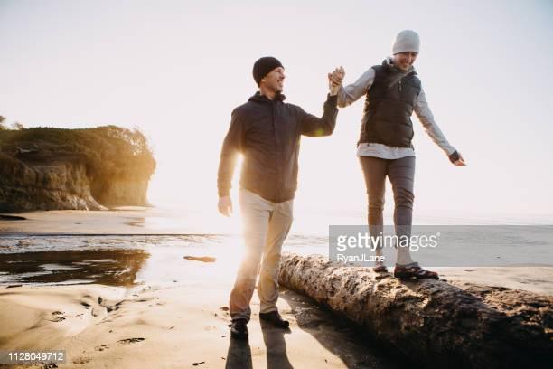 amorosa pareja jugando en la costa de oregon - equilibrio fotografías e imágenes de stock
