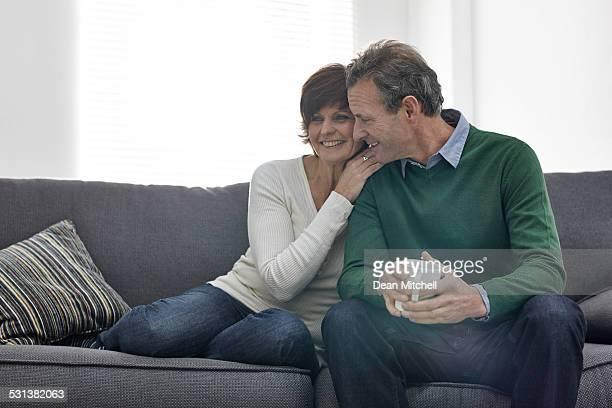 Loving マチュアカップルが一緒に座ってソファー