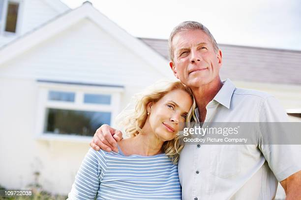 loving mature couple standing in front of their house - in front of stock pictures, royalty-free photos & images