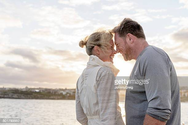 Loving mature couple touching noses by water in sunlight