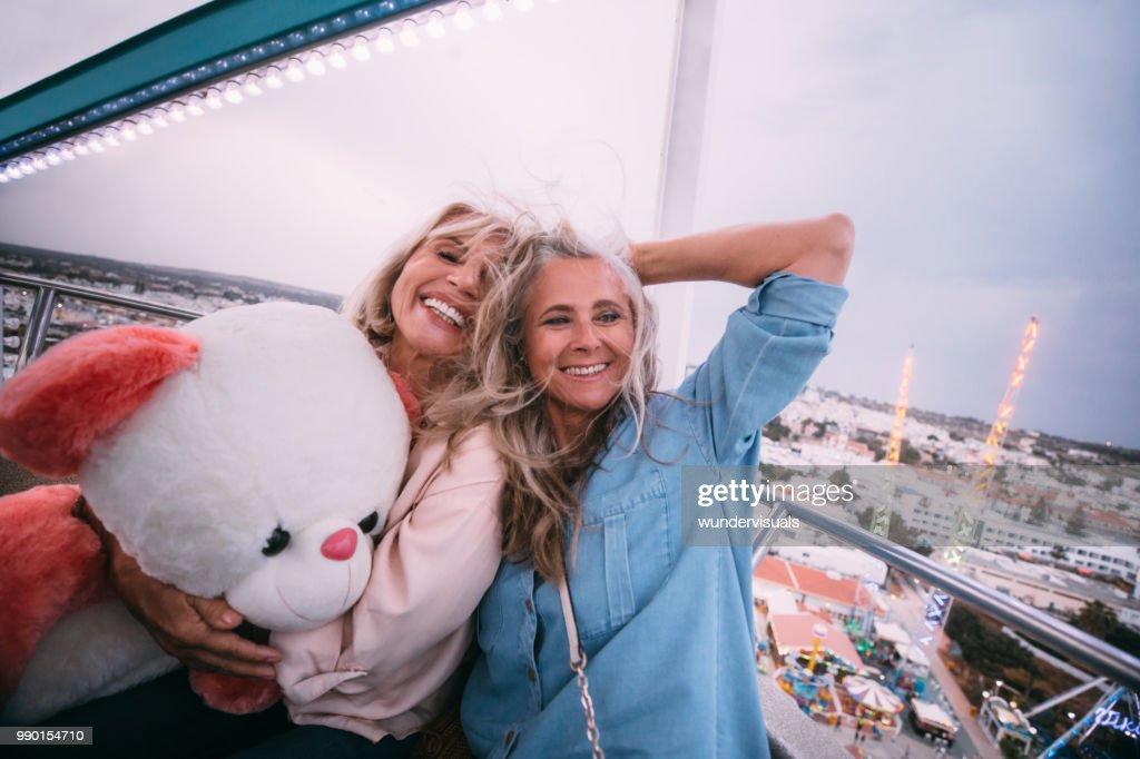 Loving mature friends laughing on amusement park ferris wheel ride : Stock Photo