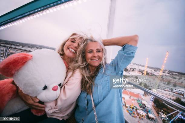 loving mature friends laughing on amusement park ferris wheel ride - ferris wheel stock pictures, royalty-free photos & images
