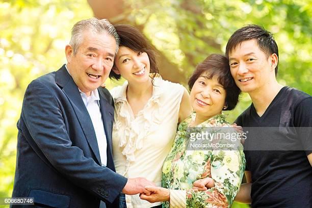 Loving mature Japanese family portrait in park