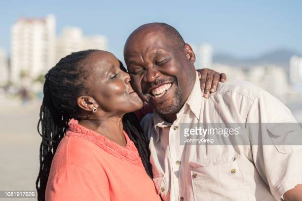 loving mature woman kissing cheerful husband's cheek - cheek stock pictures, royalty-free photos & images
