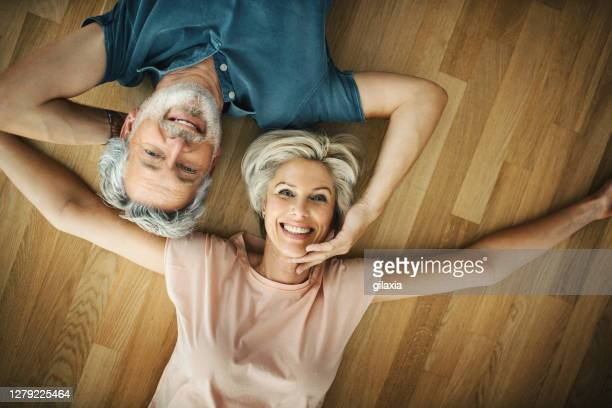loving mid aged couple at home. - human limb stock pictures, royalty-free photos & images