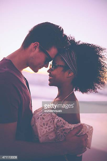 Loving mixed race couple on a beach at sunset