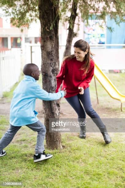 公園でタグを演奏するお母さんと黒い美しい息子を愛する - 鬼ごっこ ストックフォトと画像