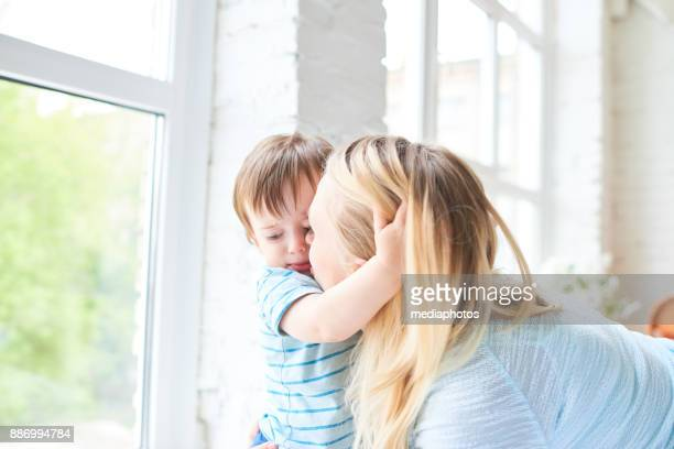 loving mom kissing son - sad mom stock pictures, royalty-free photos & images