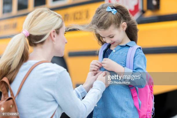loving mom prepares daughter for first day of school - unbuttoned shirt stock photos and pictures