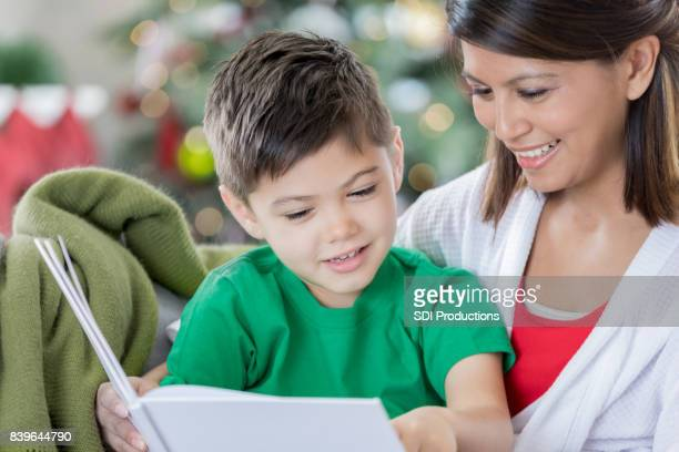 loving mom reads young son a book on christmas eve - filipino christmas family stock pictures, royalty-free photos & images
