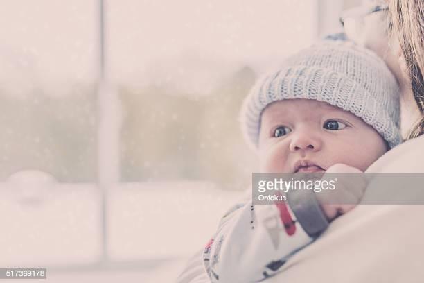 Liebevolle Mutter mit Neugeborenen Baby in der Nähe der Fenster im Winter