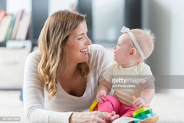 Loving mother and baby smile at one another