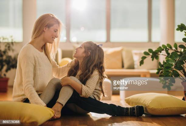 Loving mother and daughter talking to each other at home.