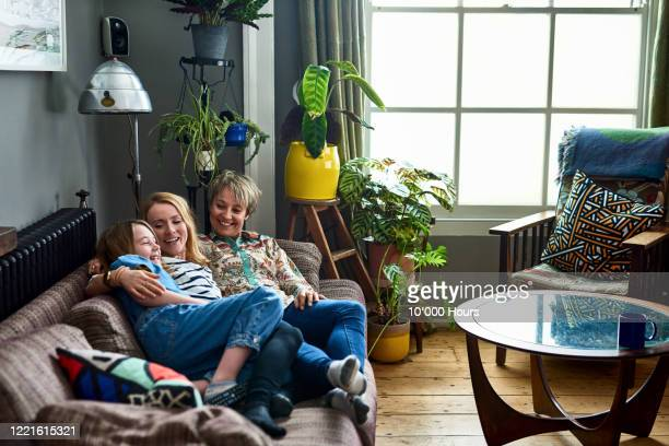 loving mother and female partner resting on sofa with daughter - lgbtq  and female domestic life fotografías e imágenes de stock