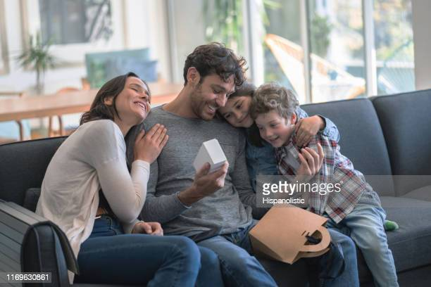 loving mother and kids celebrating father;s day hugging daddy while he opnes a present all smiling - fathers day stock pictures, royalty-free photos & images