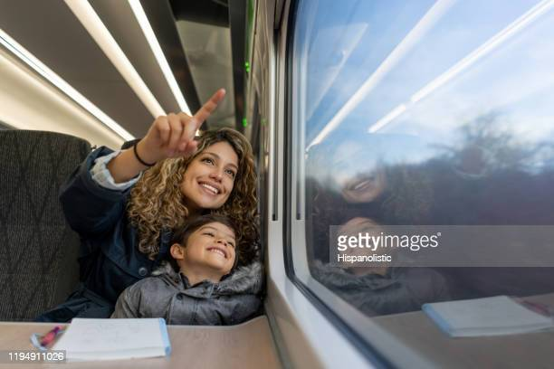 loving mother and son pointing at the window view while traveling by plane both smiling - journey stock pictures, royalty-free photos & images