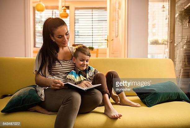 Loving mother and son reading book together at home.