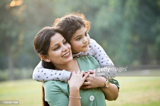 loving mother carrying her daughter at park - primary age child stock pictures, royalty-free photos & images
